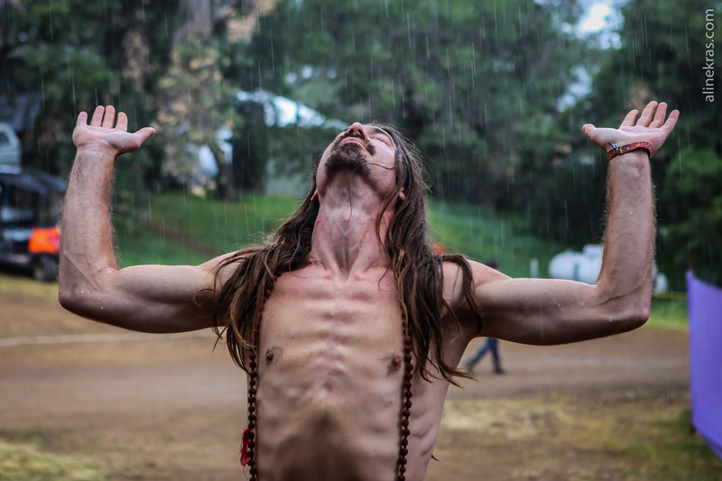 A man with long hair and no shirt feels the rain on his skin.