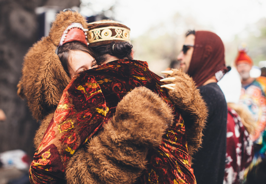 a woman in a bear costume hugs a man in a velvet jacket